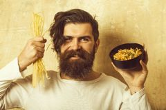 Cooking raw spaghetti in restaurant. Healthy food and dieting. Man smiling with pasta in hand. Cook or chef bearded man with bowl. Hipster hold Italian royalty free stock photo