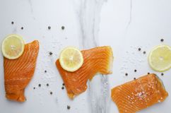 Top view of tasty salmon with different spieces on marble table royalty free stock photo