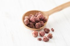Dried fruits raspberries in wooden spoon on white wooden table. Cooking recipes at home. Spices in a wooden spoon on a white table Royalty Free Stock Image