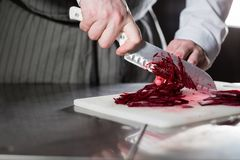 Cooking in a restaurant kitchen. Closeup of hand with knife cutting fresh vegetable. Young chef cutting beet on a white Royalty Free Stock Photos