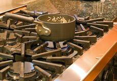 Cooking Rice. Sauce pan with rice on a six burner gas range Royalty Free Stock Photo