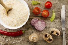 Cooking rice on aged wooden background. Cut onion, mushrooms. Chile pepper, cherry tomatoes, green salad. Healthy eating, diet Royalty Free Stock Photos