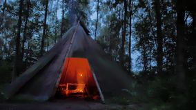 Cooking roasted meat in a Cozy tipi  in the dark scandinavian forest stock footage