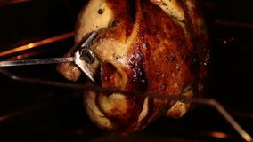 Cooking roasted whole chicken on the rotisserie spit in grilled oven. Browned chicken rotates during broiling under a grill elemen. T. Inside view stock video footage