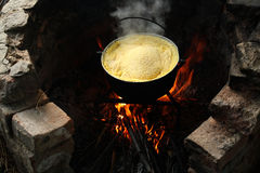 Cooking Romanian polenta (hominy). Romanian traditional food, polenta cooked in kettle Stock Photo