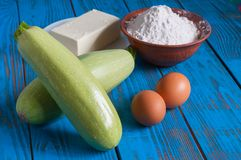 Cooking in rural kitchen - dough recipe. Ingredients eggs, flour, butter and vegetable marrow screen on vintage blue wood table from above Royalty Free Stock Image