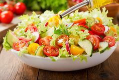 Cooking salad. olive oil pouring into bowl of fresh salad stock photo