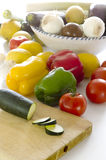 Cooking a salad. You can see in a white table various vegetables: lemons, tomatoes, onions, garlic, zucchini, peppers, cucumbers, leeks. Some are in a salad bowl Royalty Free Stock Photography