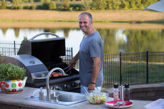 Cooking Salmon. Middle age man cooking salmons at the outside kitchen barbecue Royalty Free Stock Photography