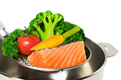 Cooking salmon and vegetables. Cooking fresh salmon fillet and vegetables, ingredients in a steel kettle on white background Stock Photography