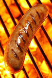 Cooking a sausage hot dog on barbecue grill Stock Photo