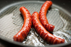 Cooking sausages Royalty Free Stock Photo