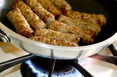 Cooking sausages in a pan Royalty Free Stock Image