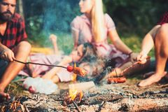 Cooking sausages on sticks over flames of campfire, overnight camping in summer. Group of friends sitting by bonfire.  royalty free stock photography