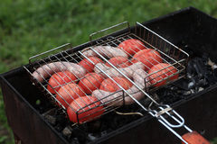 Cooking sausages with tomatoes Stock Photography