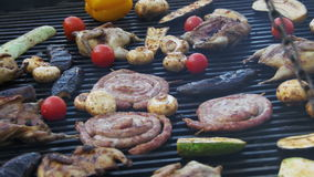 Cooking of sausages and vegetables on the grill. Cooking of meat and vegetables on the grill. hand using tongs for turning meat on the barbecue. sausages stock video footage