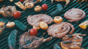 Cooking of Sausages and Vegetables on the Grill. Cooking of Meat and Vegetables on the Grill. Hand Using Tongs For Turning Meat on the Barbecue. Sausages stock footage
