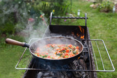 Cooking shakshuka in the pan on the grill. Boiling on blackened skillet shakshuka. Frying pan heated on the grill with coals in the garden stock photos