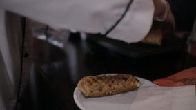 Cooking Shawarma in the restaurant. The Browning process with the help of grill. Woman cook in a roadside restaurant prepares Shawarma. Woman chef puts the stock footage