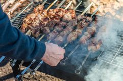 Cooking shish kebab on a charcoal grill. White man cooking shish kebab on a barbecue grill over charcoal Stock Photos