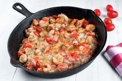 Cooking shrimp and cherry tomatoes in skillet Royalty Free Stock Images