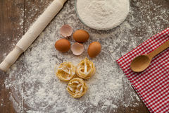 Cooking some tasty food, overhead. Cooking some delicious thing with chicken eggs, flour and pasta. View from above Royalty Free Stock Images