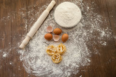 Cooking some tasty food, overhead. Cooking some delicious thing with chicken eggs, flour and pasta. View from above Stock Photos