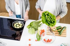 Cooking some veggie food. Couple cooking some veggie food with salad, zucchini and tomatoes on the modern kitchen, close-up view Royalty Free Stock Image