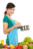 Cooking something. Beautiful young woman cooking something with vegetables on the table royalty free stock photography