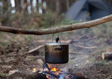 Cooking in sooty cauldron on campfire. At forest Stock Image