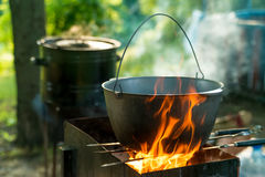 Cooking in sooty cauldron on campfire at forest. Cooking in sooty bowler on campfire at forest during hike Royalty Free Stock Photos