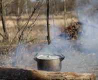 Cooking in sooty cauldron on campfire. At spring forest Stock Photo