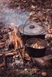 Cooking in the sooty cauldron on the open fire in woods. Cooking food at a campsite in wood Stock Image