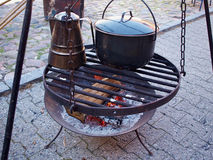 Cooking soup over burning campfire Stock Images
