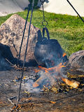 Cooking soup over burning campfire Royalty Free Stock Photography