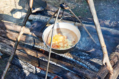Cooking soup in the stowed bowler over campfire Royalty Free Stock Images