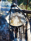 Cooking soup in the stowed bowler over campfire Royalty Free Stock Photo