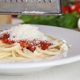 Cooking spaghetti noodles pasta grating Parmesan cheese on plate stock image