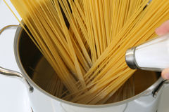Cooking spaghetti noodles pasta meal: salting water in pot Stock Photography