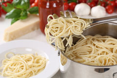 Cooking spaghetti pasta: serving noodles on plate. Cooking spaghetti pasta: serving noodles from pot on plate stock image