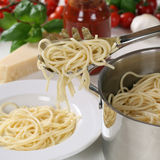 Cooking spaghetti pasta serving noodles from pot on plate Stock Image