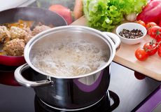 Cooking spaghetti in a pot with boiling water. On a cooker on a kitchen royalty free stock photo