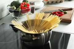 Cooking spaghetti in pot. On electric stove stock image