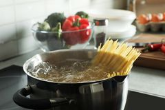 Cooking spaghetti in pot. On electric stove royalty free stock photography