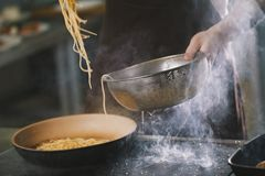 Cooking spaghetti in restaurant Stock Photo