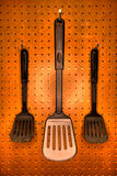 Cooking Spatulas. Professional cooking utensils in a restaurant kitchen, hanging o a pegboard wall Royalty Free Stock Photo