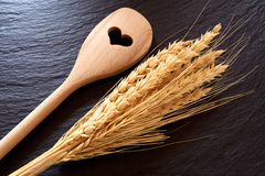 Cooking spoon and cereal ears. Wooden cooking spoon and golden cereal ears on black slate platter Stock Image
