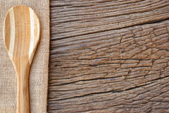 Cooking Spoon on jute fabric. Wooden cooking Spoon on jute fabric on a rustic wooden background with copy space as menu card Royalty Free Stock Photography