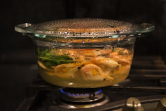 Cooking srimps in transparent glass pot. On gas oven Royalty Free Stock Photo