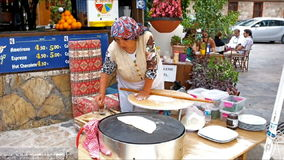 Cooking in the street. ANTALYA, TURKEY - MAY 6, 2017: The senior cook rolls the dough for gozleme - tastyTurkish flatbread, on May 6 in Antalya stock footage